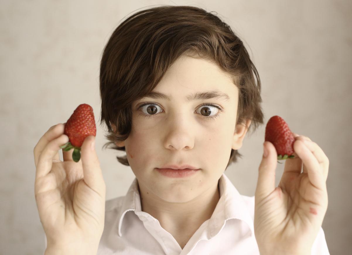 Niño con fresas en las manos