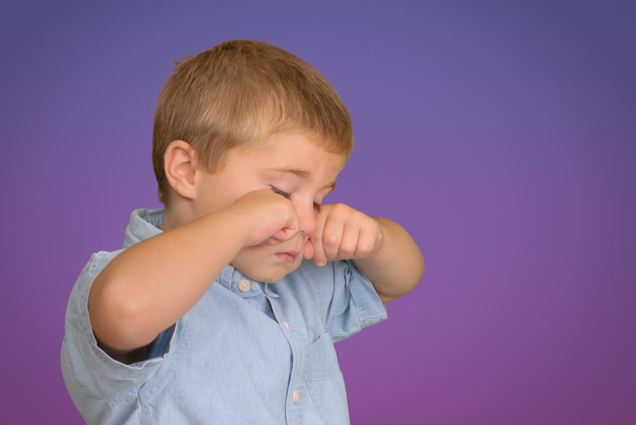 Niño con camisa azul frotándose los ojos