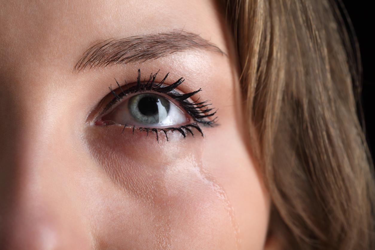 Mujer con ojos verdes llorando y mirando hacia arriba