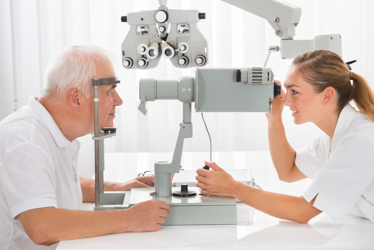 Hombre canoso con polo blanco en revisión oftalmológica