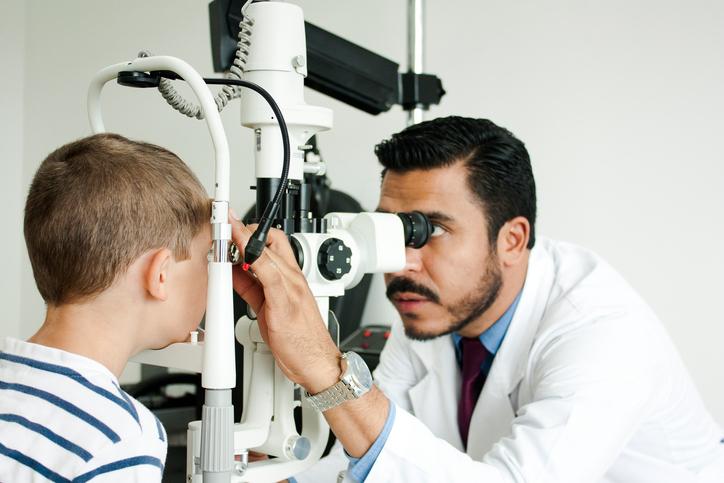 Niño revisándose la vista en el oftalmólogo