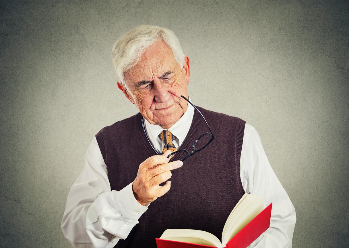Hombre canoso con gafas en la mano leyendo un libro rojo