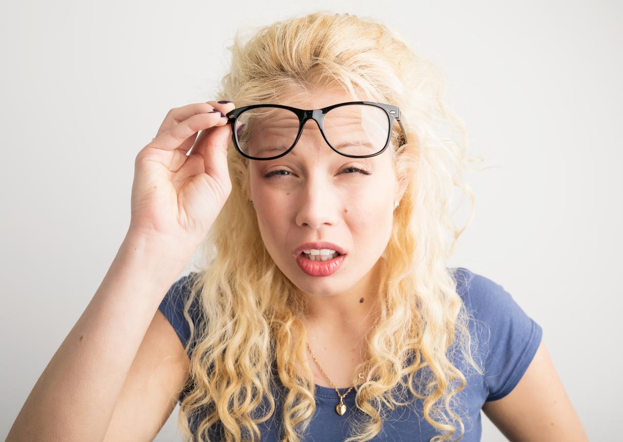Mujer rubia se levanta las gafas para ver