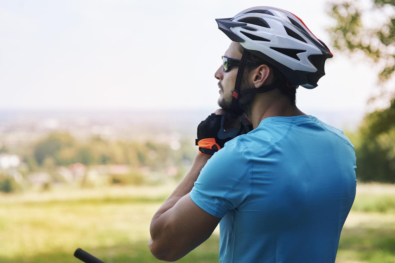 Hombre atándose un casco para hacer ciclismo