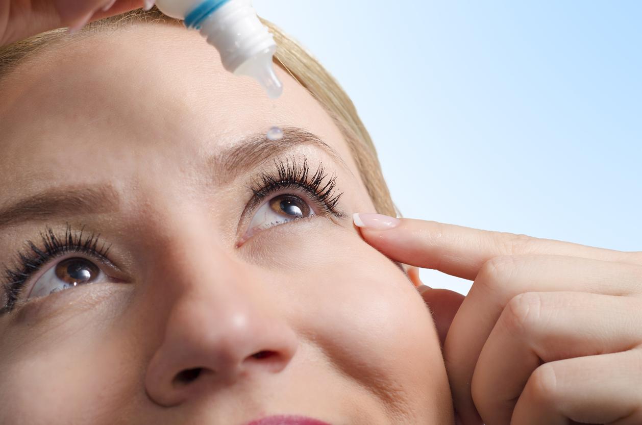 Mujer rubia echándose gotas en un ojo