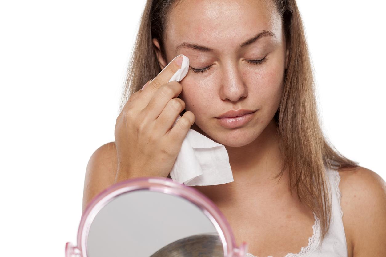 Chica limpiándose los párpados con una toallita en su rutina de higiene ocular