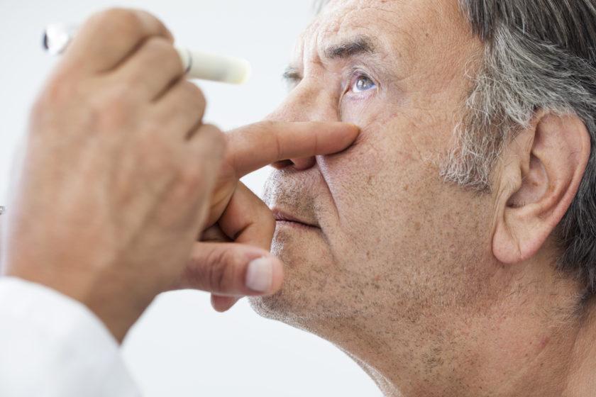 Primer plano mano de oftalmólogo que revisa la vista a un hombre