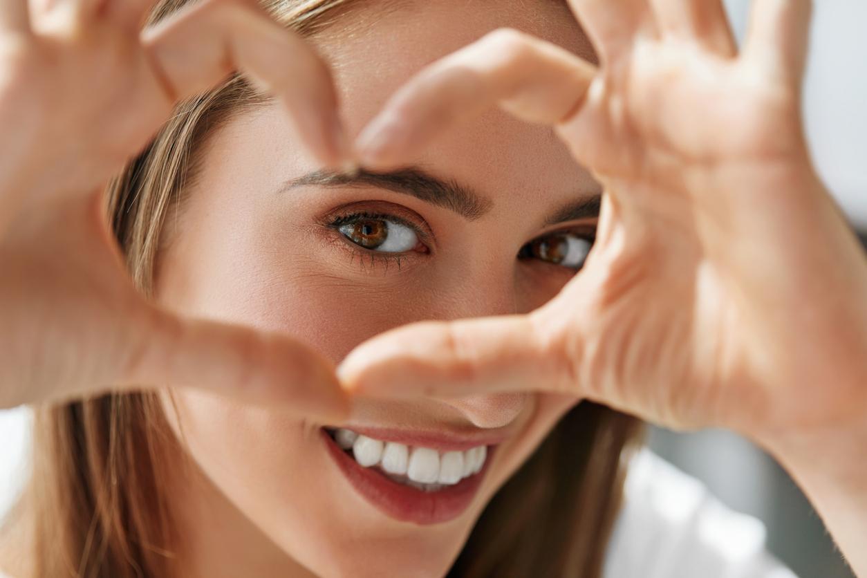 Mujer haciendo un corazón frente a sus ojos