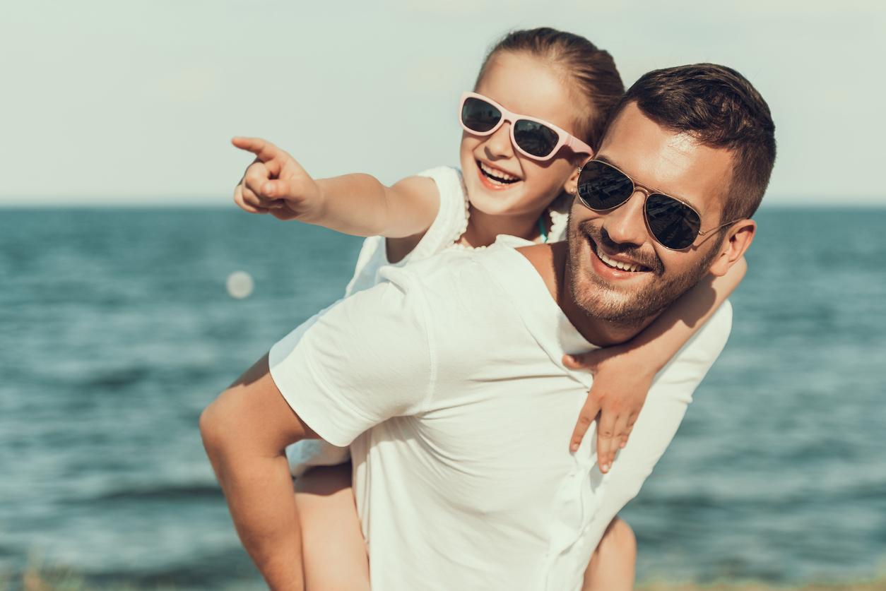 Padre con su hija en la playa y ambos usan gafas de sol