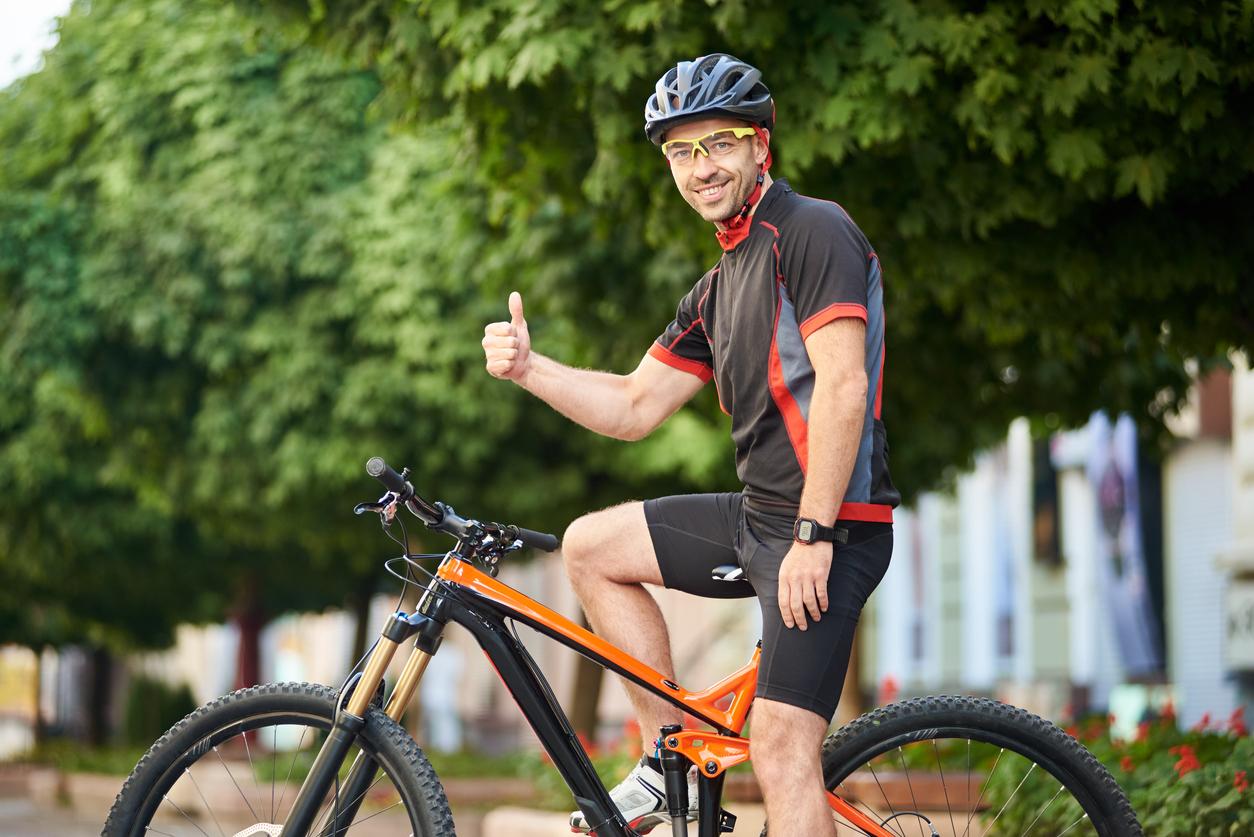 Ciclista montado en bicicleta y haciendo el signo de OK