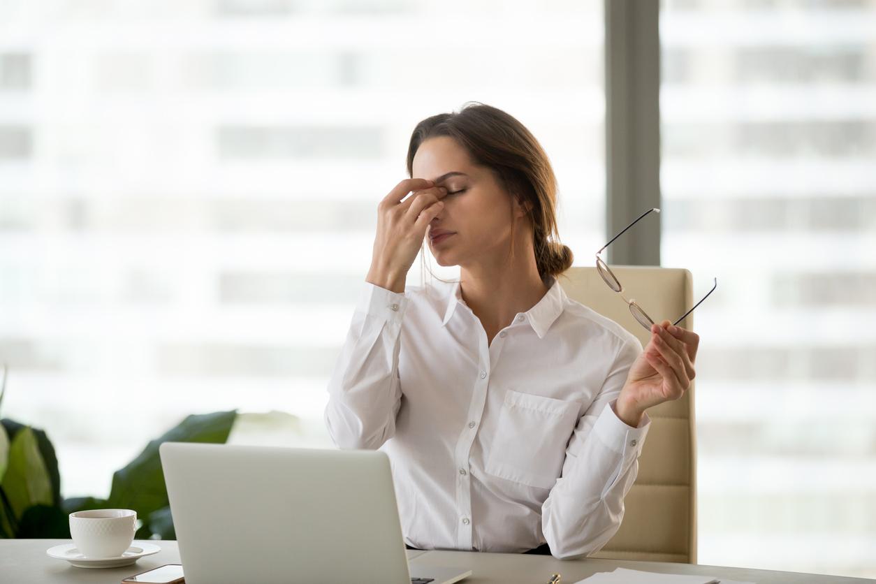 Mujer con camisa blanca se frota los ojos con las gafas en la mano