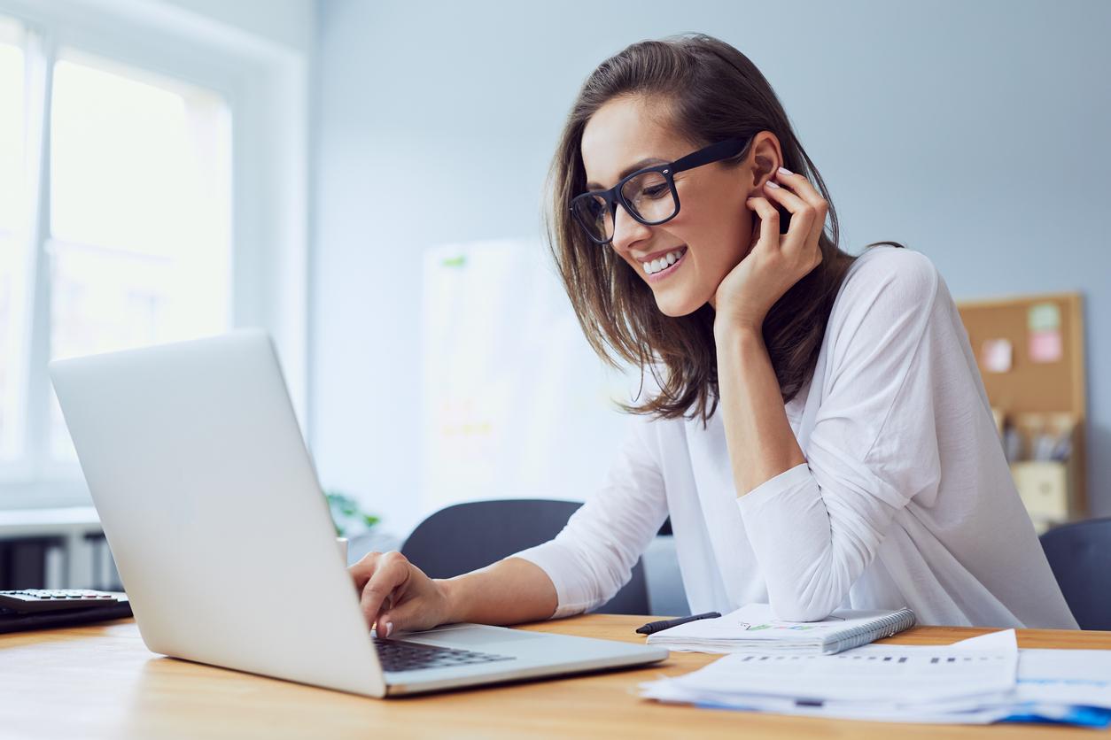 Chica con gafas ocupacionales riéndose frente al ordenador