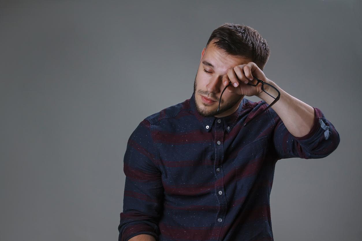Hombre joven con camisa se quita las gafas y se frota un ojo
