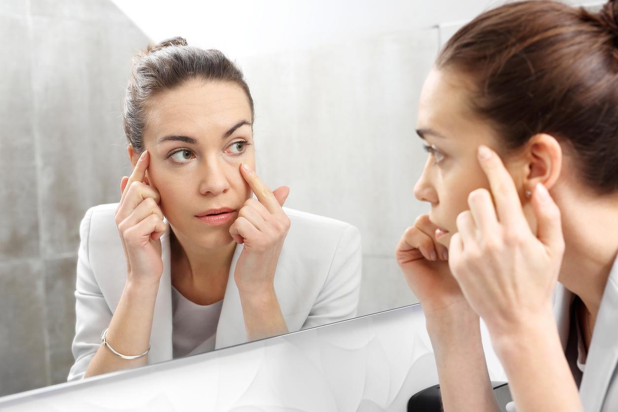 Mujer morena con moño se mira al espejo y se señala un ojo