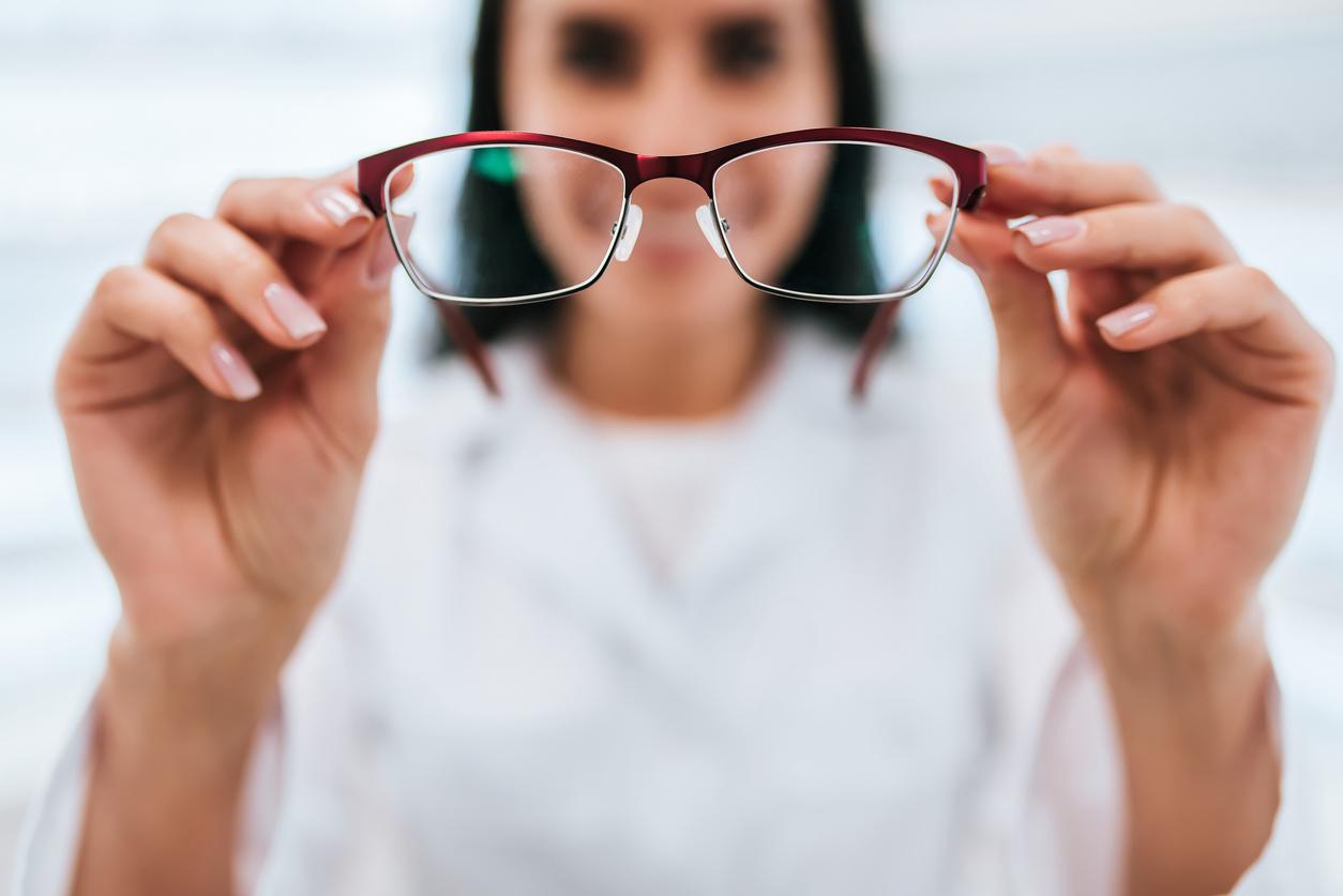Mujer con bata blanca enseña unas gafas con montura roja