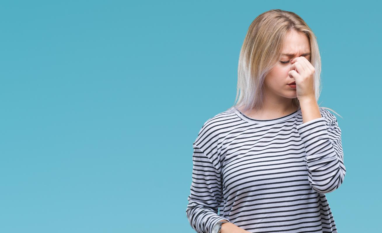 Mujer con camiseta a rayas se frota los ojos