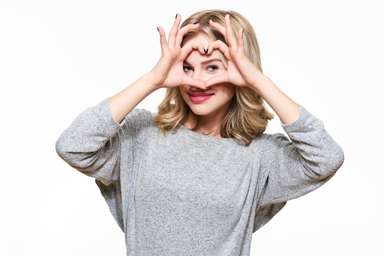 Mujer con jersey gris hace un corazón con sus manos