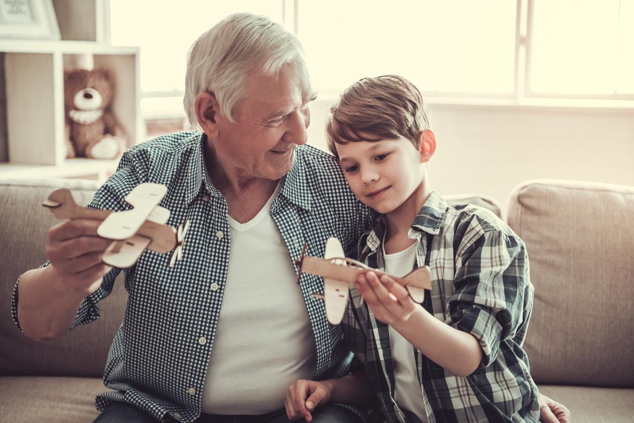 Hombre mayor jugando con niño con aviones de madera