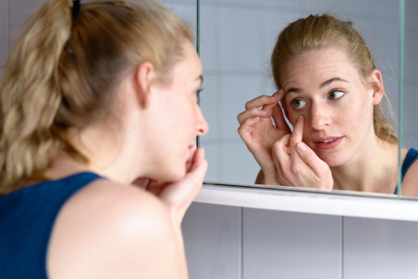 Mujer mirándose un ojo en el espejo