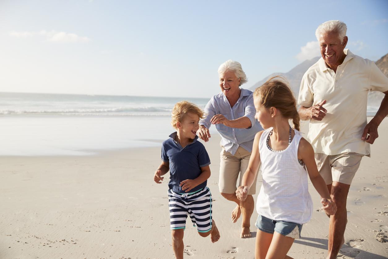 Pareja de ancianos corriendo por la playa con pareja de niños