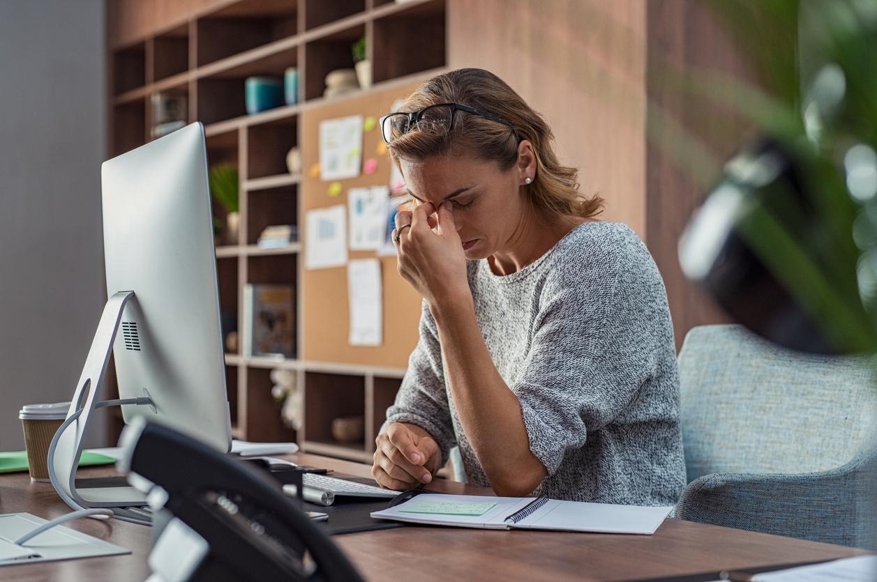 Mujer con dolor de cabeza en la oficina