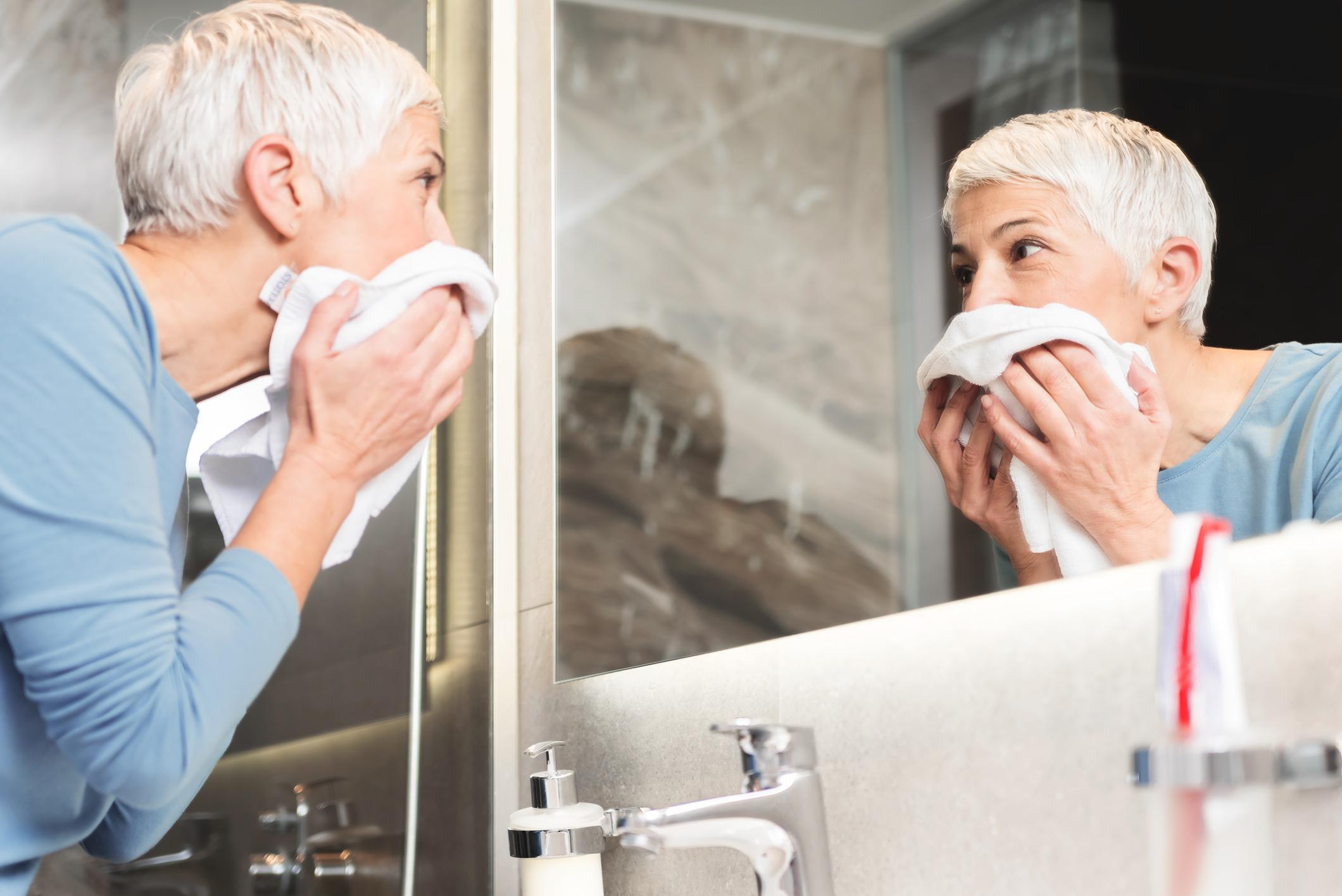Mujer rubia de pelo corto lavándose la cara