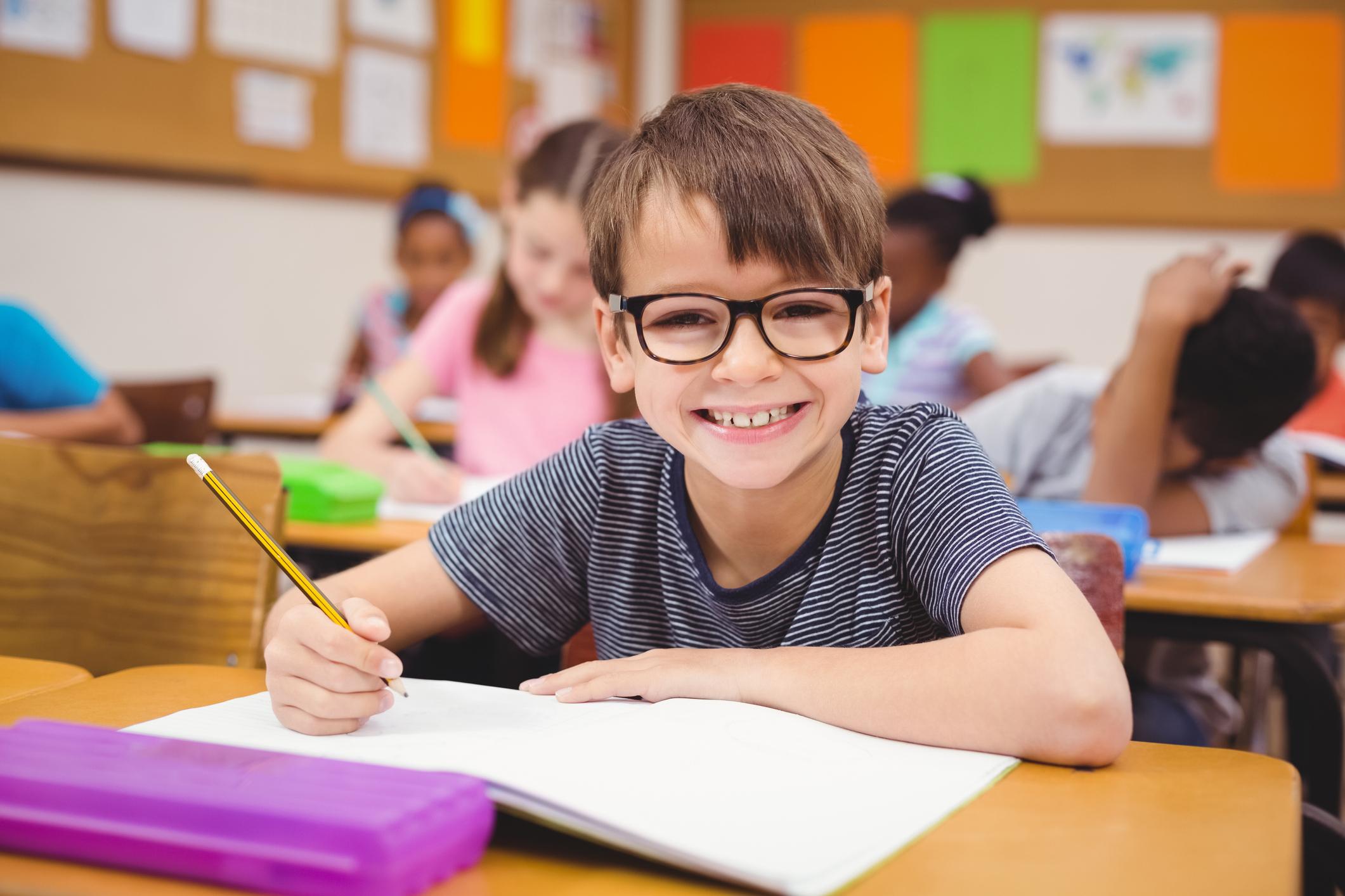 Niño con gafas sonríe a la cámara en un aula