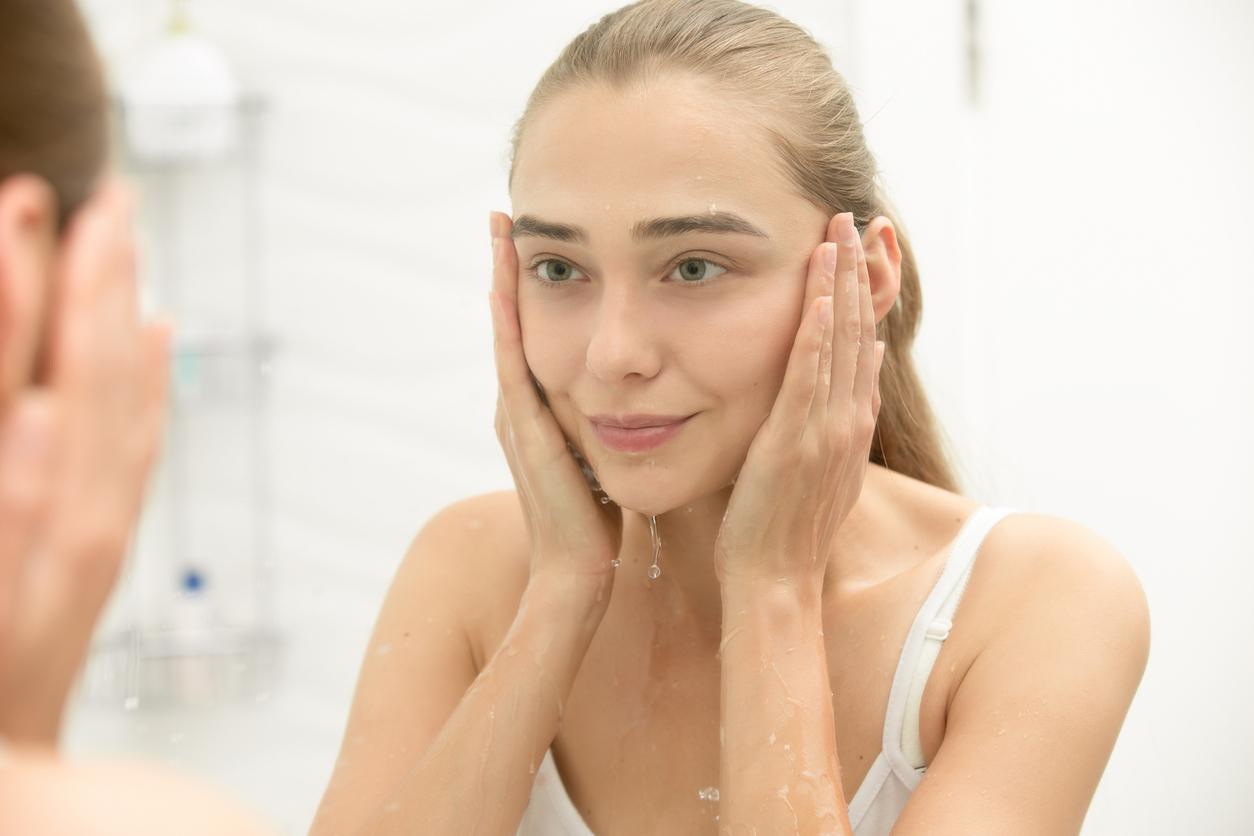 Mujer rubia lavándose la cara