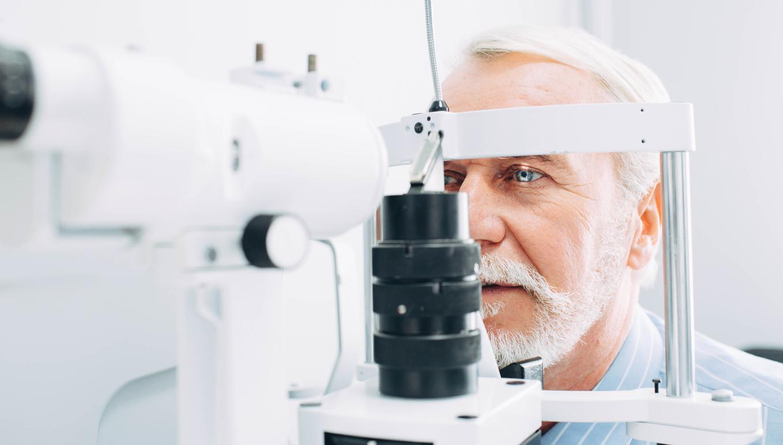 Hombre canoso con barba se revisa la vista