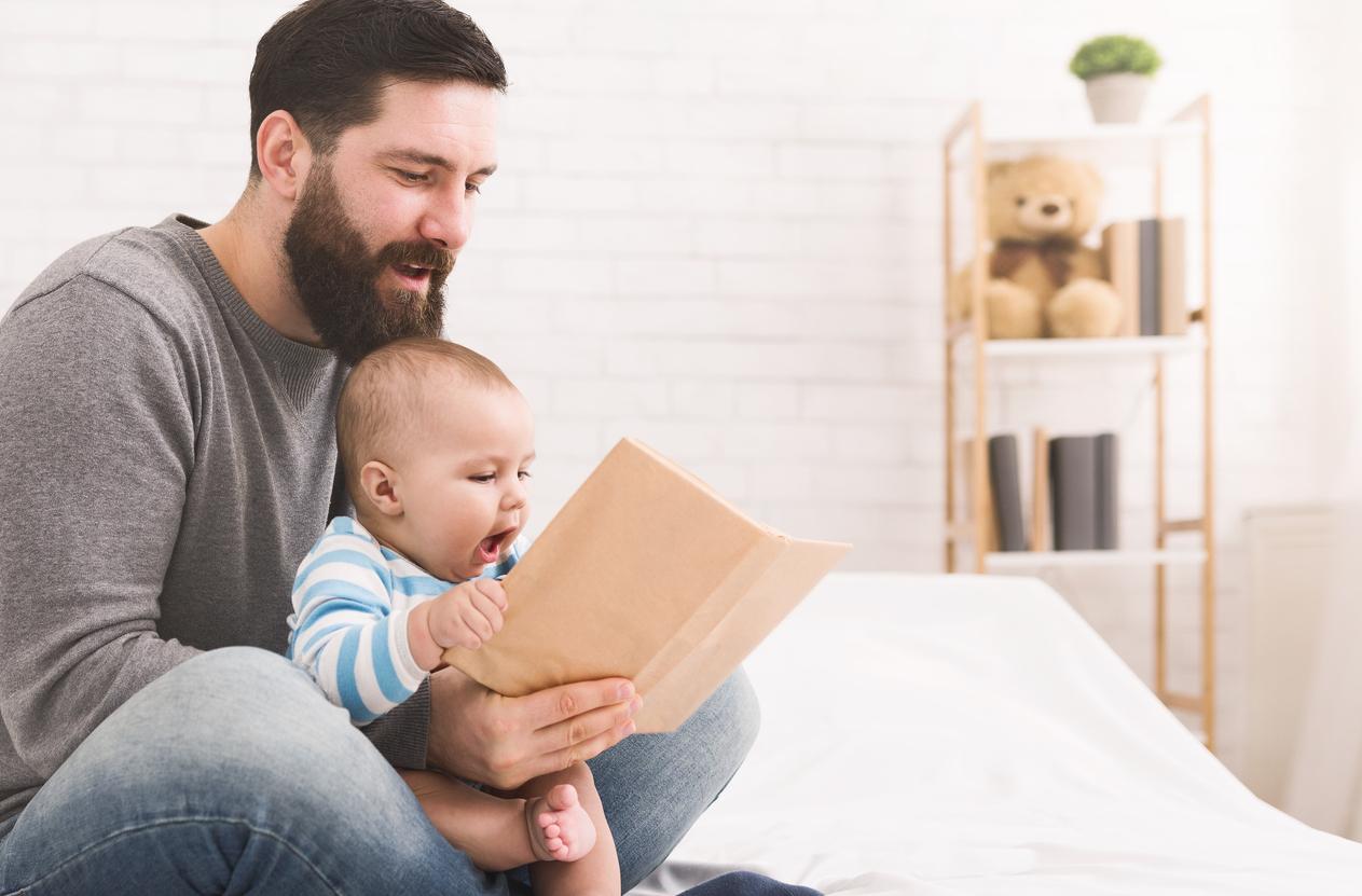 Padre mirando un libro con un bebé