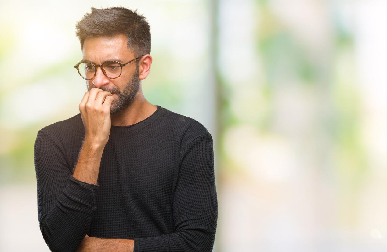 Hombre con gafas se muerde las uñas