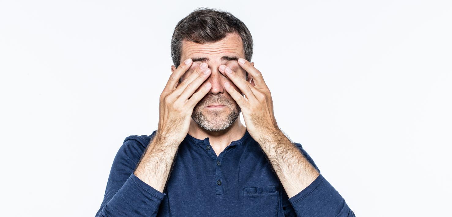 Hombre con camiseta azul se frota los ojos