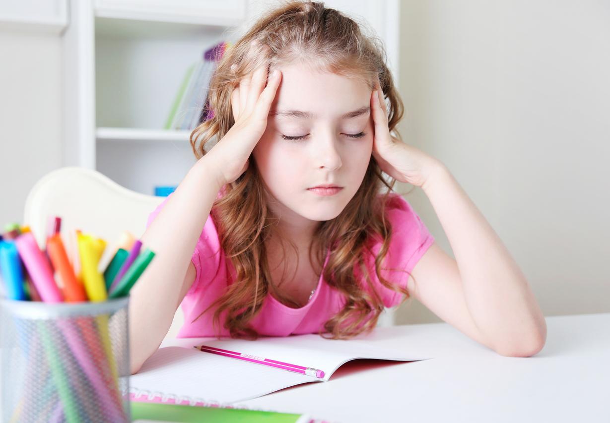 Niña con camiseta rosa y dolor de cabeza
