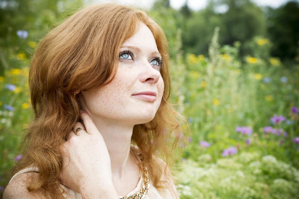 Chica pelirroja en el campo mira al cielo