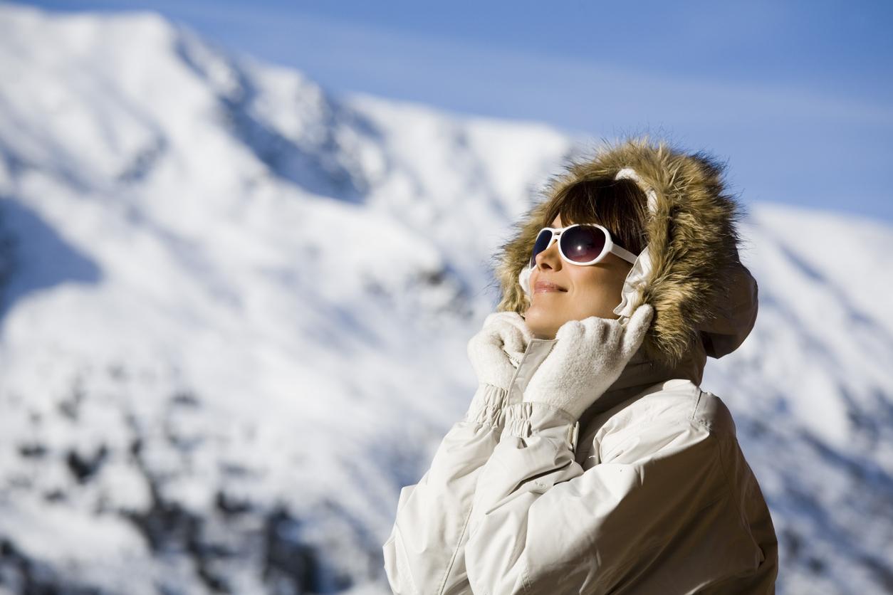 Chica en la nieve con gafas de sol