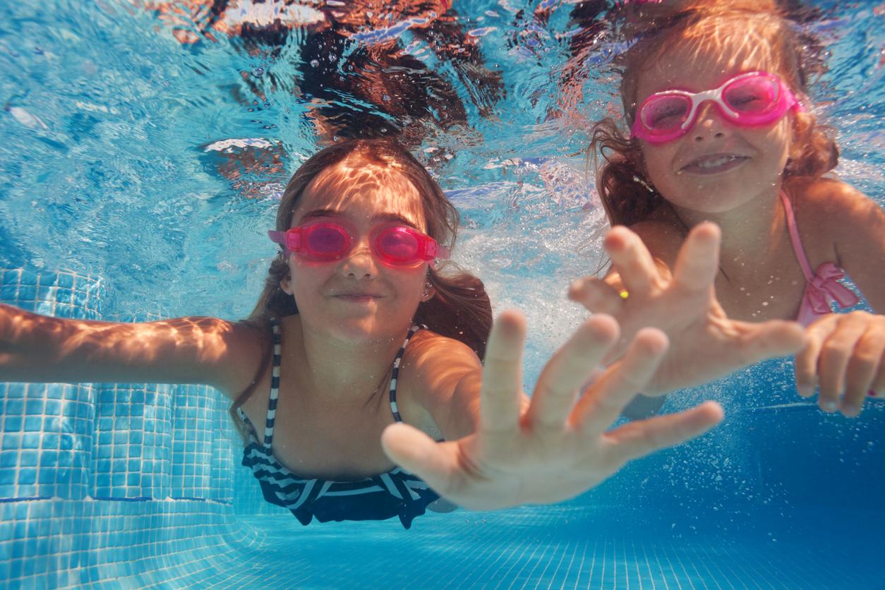 Niñas debajo del agua en la piscina