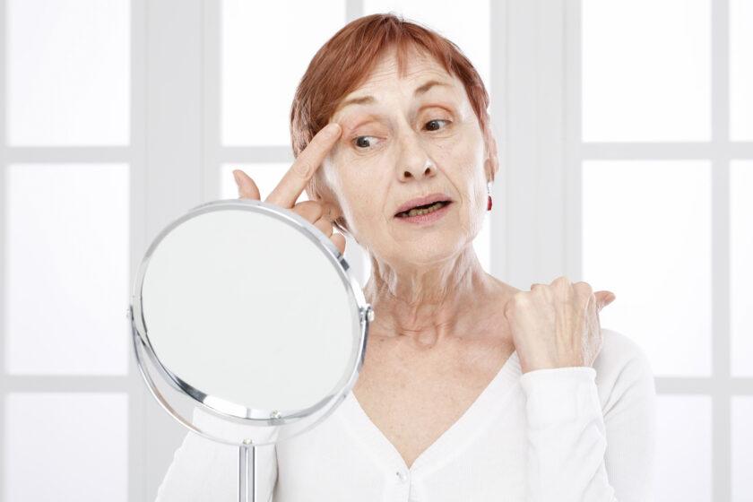 Mujer mirándose al espejo y levantándose un párpado