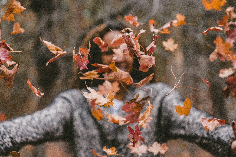 Chica lanzando hojas en otoño