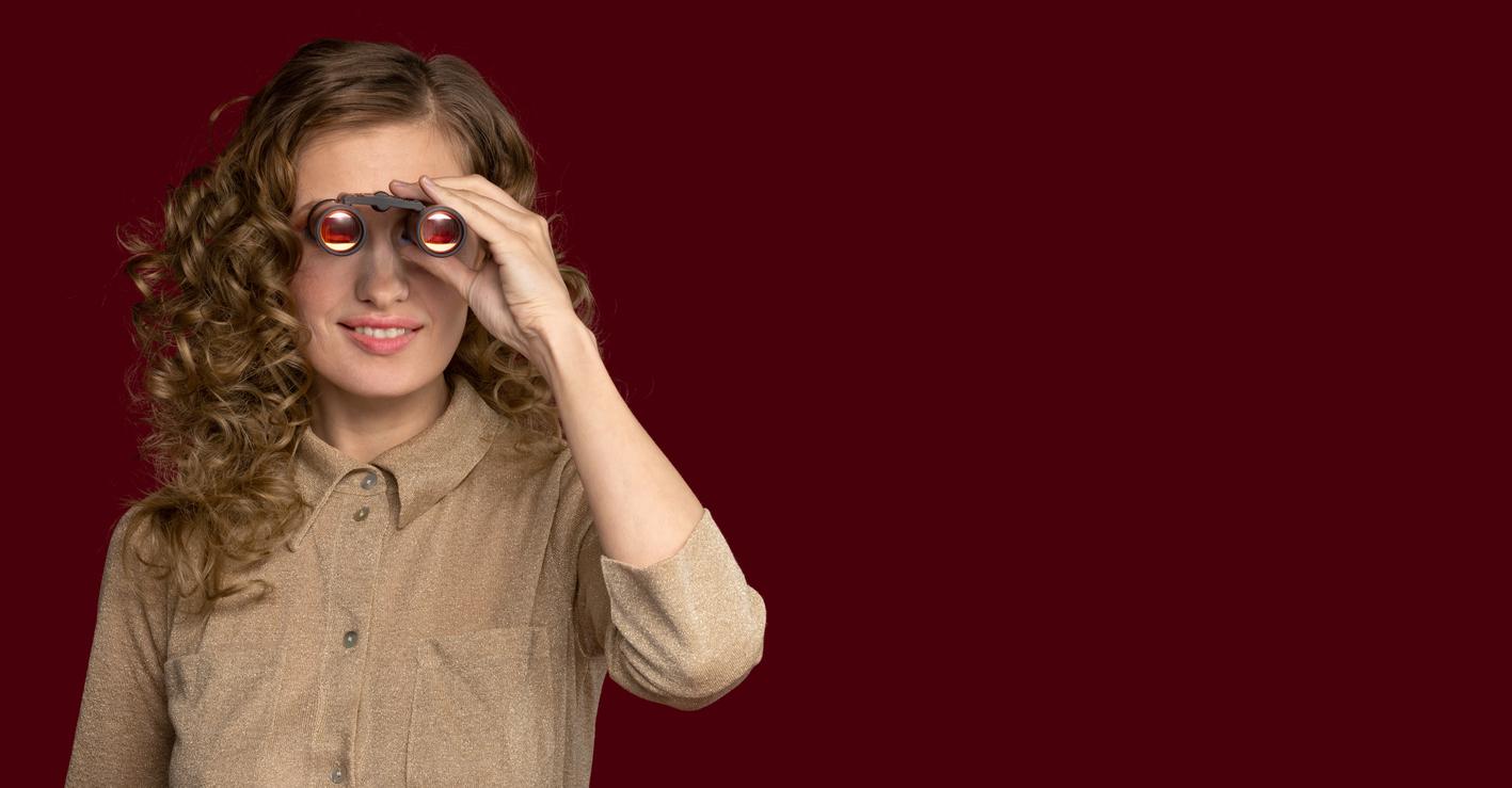 Mujer con el pelo rizado mirando por prismáticos