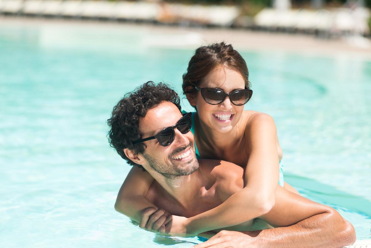 Pareja en una piscina con gafas de sol