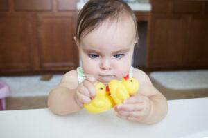Niña jugando con patos de goma