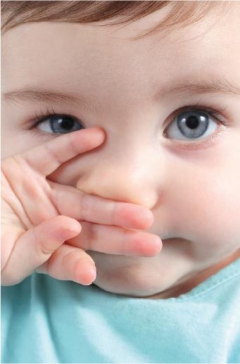 Bebé pelirrojo con ojos azules se tapa la boca
