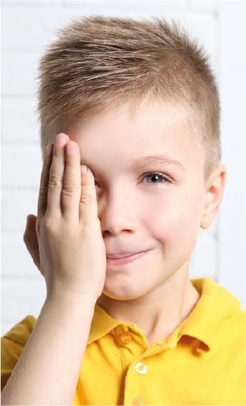 Niño rubio con polo amarillo se tapa un ojo