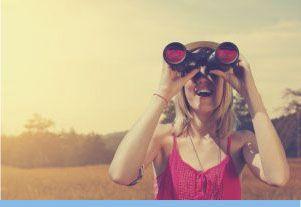 Mujer con camiseta roja mirando por prismáticos